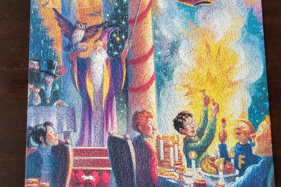 finished puzzle of a scene from Christmas at Hogwarts showing Harry at a table with three of the Weasley boys watching him open a wizard cracker that contains a pirate hat. Hagrid, McGonagall, Cho, and Dumbledore look on. Dumbledore is holding an enormous wand in one hand and an owl on his other arm