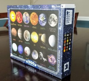Picture of the puzzle box with black background, pictures of all the planets and some moons in the solar system