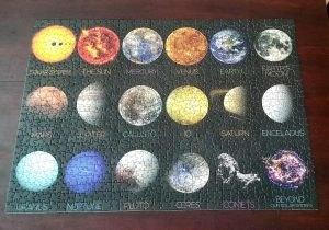 Finished puzzle of the solar system. Planets and moons are laid out in rows instead of in orbit
