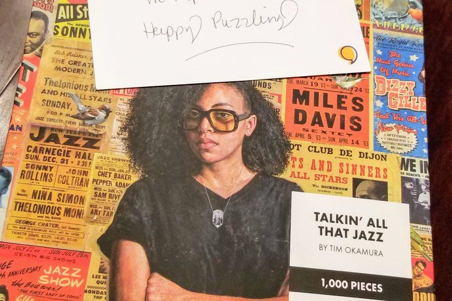 Puzzle box with old posters advertising jazz shows of various famous artists, with a black woman in the forefront wearing glasses and her arms crossed. A thank you note is placed on top of the box.