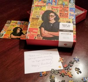 Puzzle box open with the included thank you note and actual proportioned photo of the puzzle to work from. Some puzzle pieces scattered around.