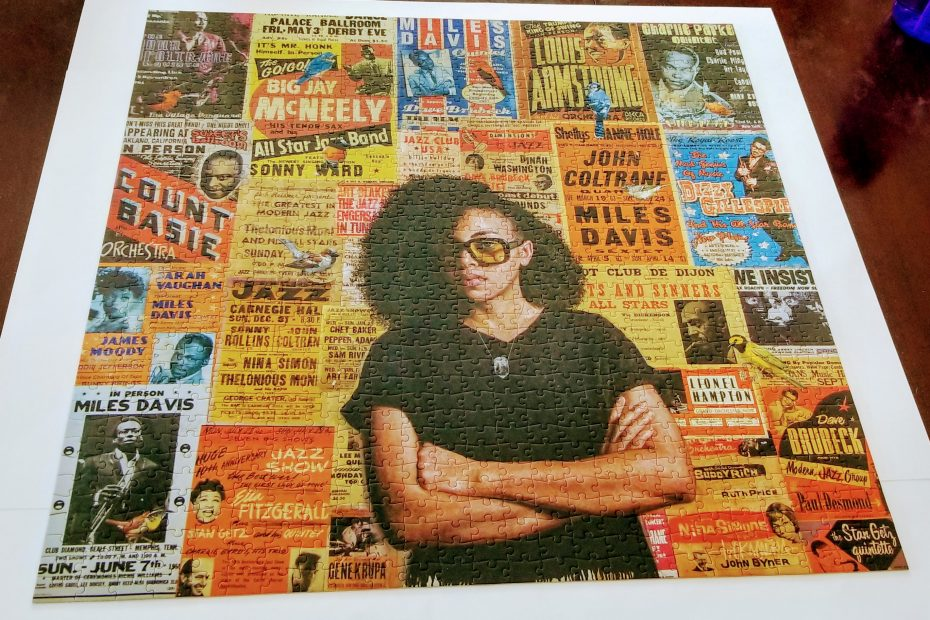 Brown skinned girl with glasses stands with arms folded in front of a wall plastered with old jazz show fliers.
